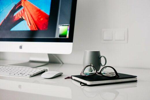 Computer, briller, en bog, en kop